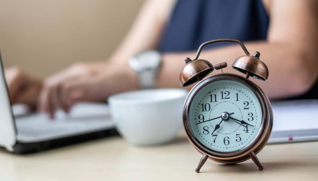 Close up alarm clock with young Businesswoman using laptop